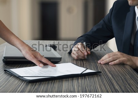 Female hand pointing to businessman at signature place on a contract document in office - stock photo