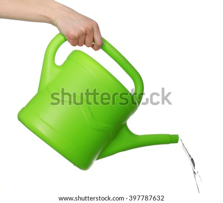 Female hand pouring from green plastic watering can, isolated on white - stock photo