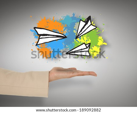 Female hand presenting paper airplanes against grey vignette