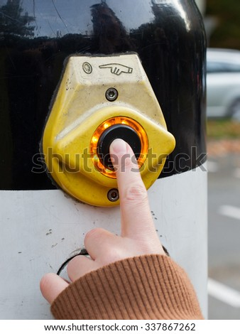 Female hand pushing button for traffic light, selective focus on button - stock photo