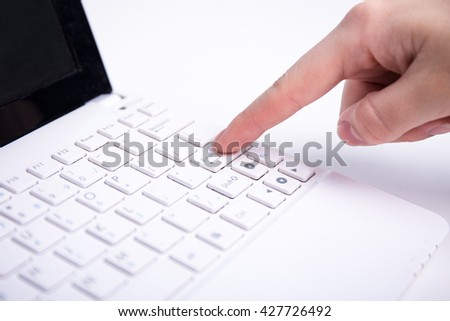 female hand pushing enter button on white laptop keyboard