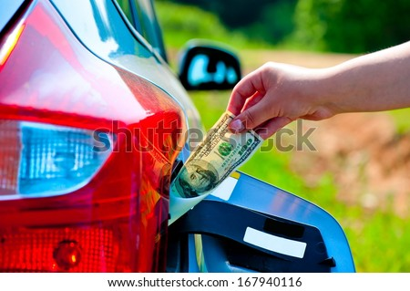 female hand puts the car into the gas tank one hundred dollars - stock photo