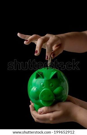 Female hand putting coin into a piggy bank on black background, isolated - stock photo