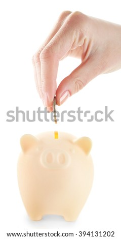 Female hand putting coin into piggy bank isolated on white