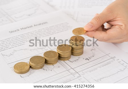 Female hand putting coin on coins stack with the report analyzes economic trends