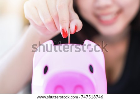 Female hand putting money into piggy bank.