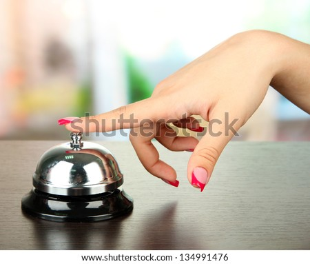 Female hand ringing in service bell on bright background