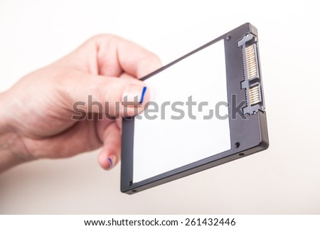Female hand showing a Solid State Drive on white