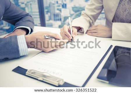 Female hand signing contract. - stock photo