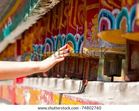Female hand spinning the prayer wheels for good karma - stock photo