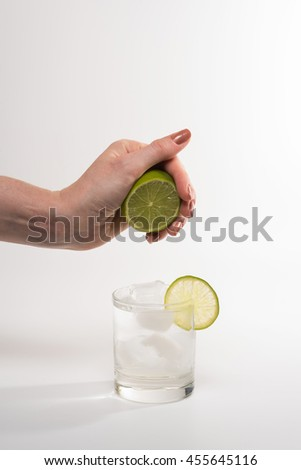 Female hand squeezing lime into glass cocktail - stock photo