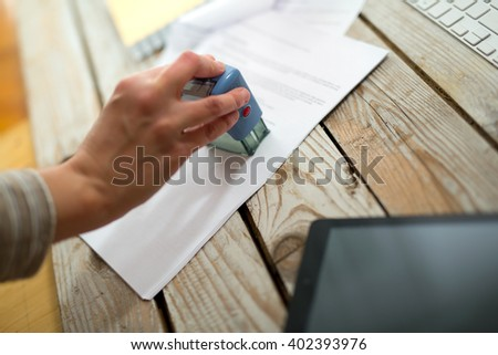Female hand stamping document, working at office - stock photo