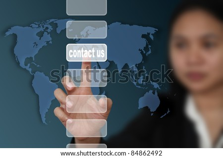 female hand touch on contact us button with world map background - stock photo