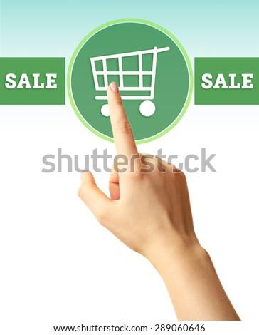 Female hand touching shopping cart symbol - stock photo