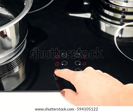 female hand turns on electric hob closeup finger presses button on modern induction cooker
