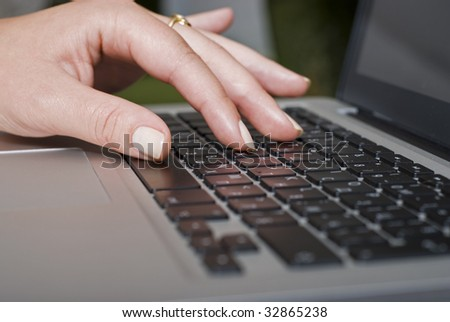 Female hand typing on a laptop keyboard, Shallow Depth-of-field