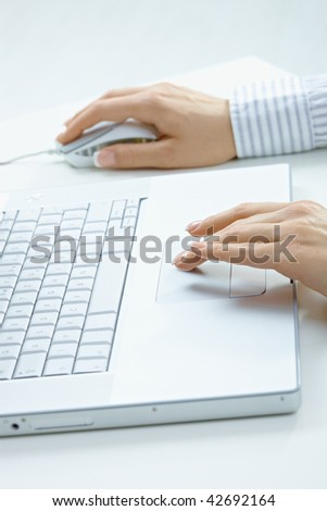 Female hand typing on computer keyboard, using mouse.