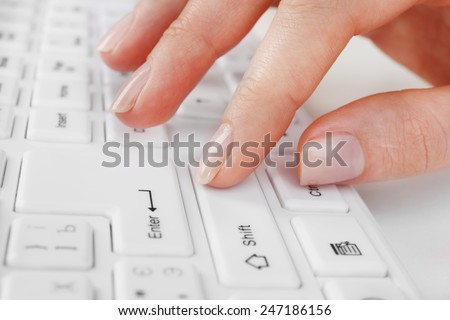 Female hand typing on keyboard, macro view - stock photo