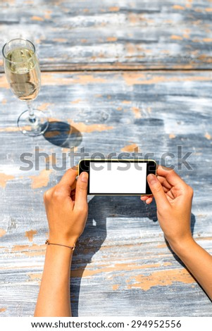 Female hand using a phone with isolated screen on wooden vintage table with a champagne - stock photo
