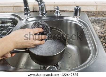 Female hand washing stainless steel pan with steel pad and soapy water in kitchen sink