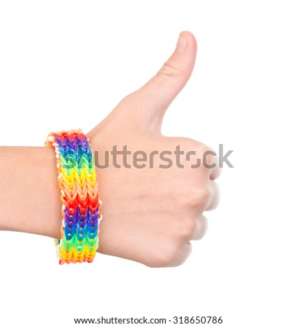 Female hand with a bracelet patterned as the rainbow flag showing thumbs up  - stock photo