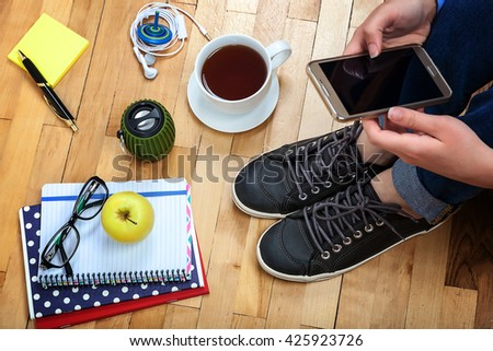 Female hand with a mobile phone, notebooks, pen, glasses, music speakers, headphones, cup of tea, apple on a wooden background.