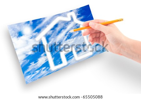 Female hand with a pencil draws a house of clouds against the sky. - stock photo