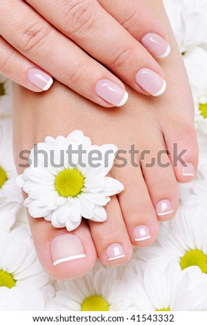 female hand with beautiful french manicure on the pure and clean foot - stock photo