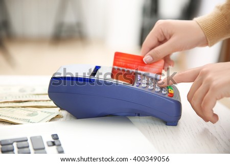 Female hand with credit card and bank terminal - stock photo