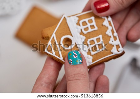 Female hand with festive  Christmas manicure  holding tasty gingerbread cookie. Christmas and New Year.
