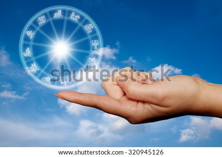 female hand with finger holding an astrological wheel - stock photo