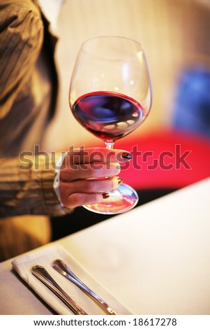 Female hand with glass of red wine. Shallow DOF. - stock photo