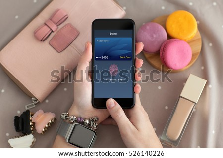 female hand with jewelry holding phone with online shopping touch and pay