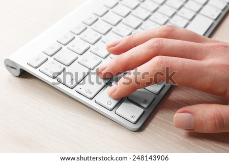 Female hand with keyboard on wooden desktop background - stock photo