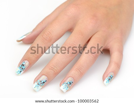 Female hand with manicure close up. Drawing of a branch with blue flowers. It is isolated on a white background. - stock photo