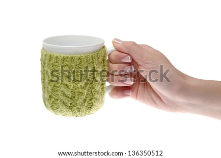 Female hand with manicure holding a cup, tied green threads - stock photo