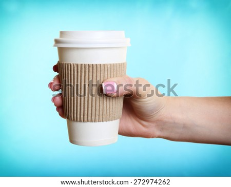 Female hand with paper cup on blue background - stock photo