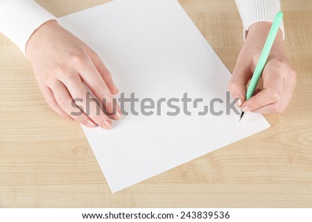 Female hand with pen and sheet of paper on wooden table background - stock photo