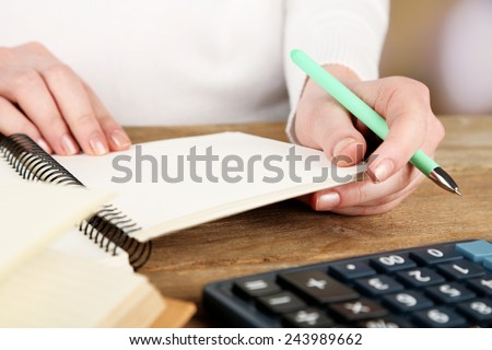 Female hand with pen, notebook and calculator at desktop on light background - stock photo