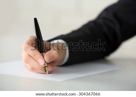 Female hand with pen writing on paper at workplace - stock photo