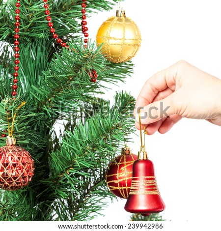 Female hand with red bell and Christmas tree isolated on white background. - stock photo
