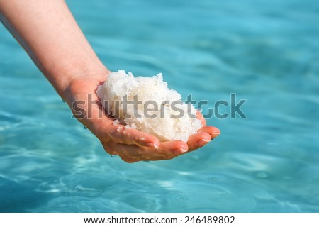 Female hand with sea salt for spa from Dead Sea - stock photo