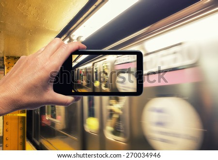 Female hand with smartphone taking a picture of New York subway train. Tourism concept. - stock photo