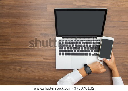 Female hand with smartwatch with holding mobile phone on laptop computer, View from above