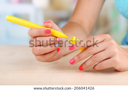 Female hand with stylish colorful nails holding felt pen, on wooden table, on bright background