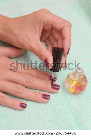 Female hand with stylish colorful nails, on color towel. Colorful oil bottles