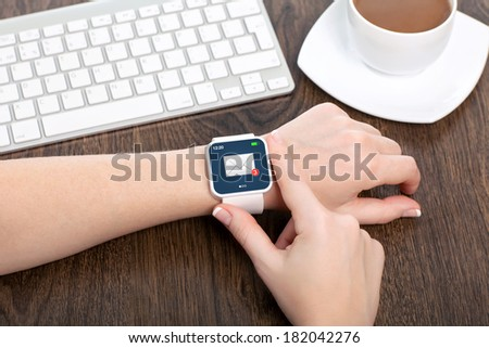 female hand with white smartwatch with email on the screen over a wooden table in an office - stock photo