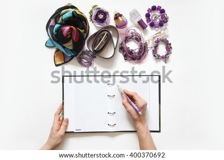 Female hand writing in a diary. Jewelry and spirits lie on a white table. - stock photo