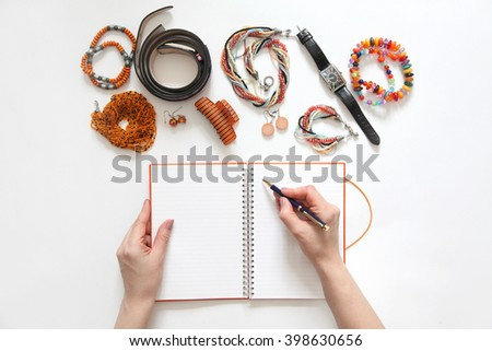 Female hand writing in diary. Colored bracelets, scarf, turtleneck, lemon color, blue, turquoise, white background. - stock photo