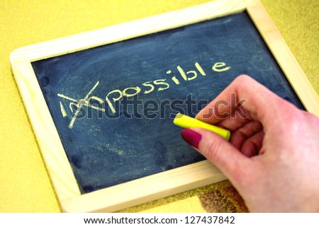 female hand writing on blackboard, impossible is possible - stock photo